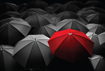 Red umbrella among black